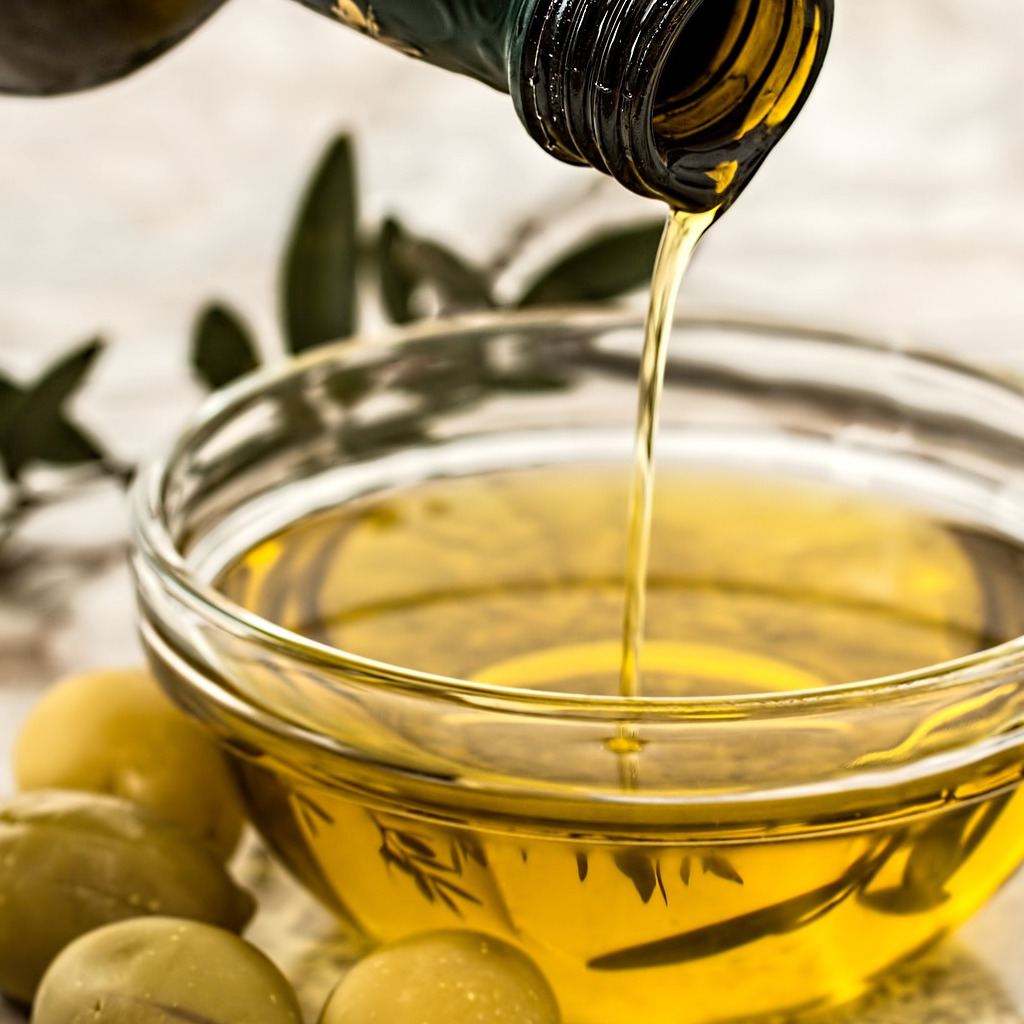 Pouring olive oil into a glass bowl