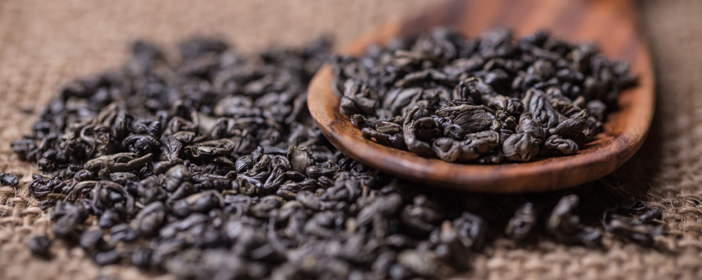 Spoonful of dry green tea leaves